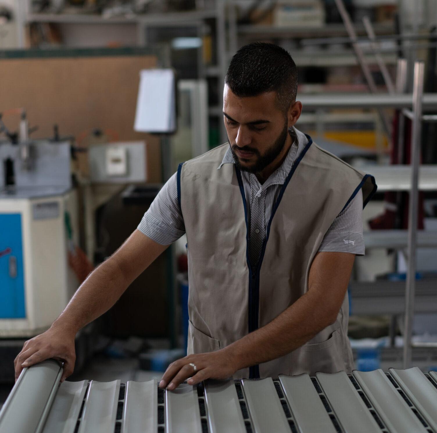 Worker fixing a window shutter at a factory